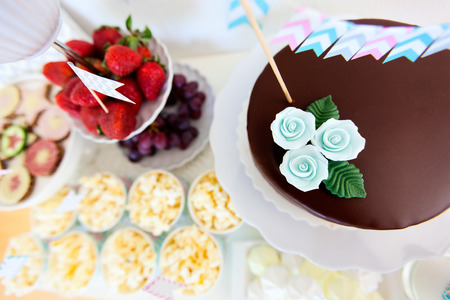 Berries, popcorn, canapes, candies and a chocolate cake on a dessert table at party photo
