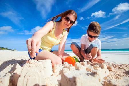 Young mother and her son at tropical beach making sandcastle Stock Photo - 29258078