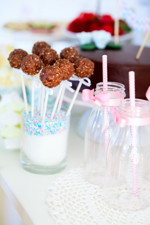 Chocolate cake pops on a dessert table at party or wedding celebration photo