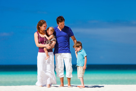 Happy beautiful family on a tropical beach during summer vacation Stock Photo - 29258484