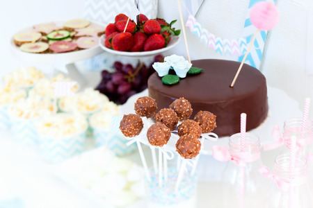 Berries, popcorn, canapes, candies, chocolate cake pops and a cake on a dessert table at party
