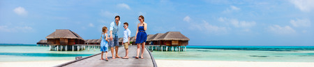 Happy beautiful family walking on wooden jetty during summer vacation at luxury resort wide panorama with copy space, perfect for banners