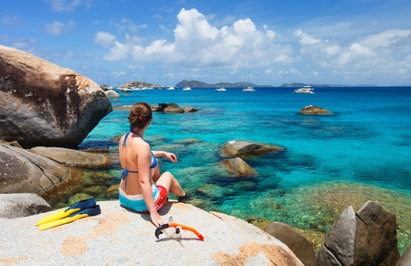 snorkelling: Young woman with snorkeling equipment enjoying view of a tropical beach sitting on granite boulder at Virgin Gorda, British Virgin Islands, Caribbean