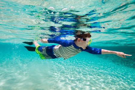열 대 해변에서 얕은 청록색 물 속에서 수 중 수영 귀여운 십 대 소년