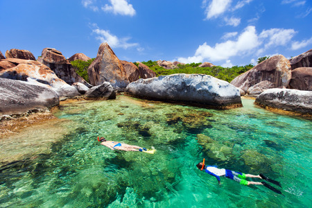 Family of young mother and son snorkeling in turquoise tropical water among huge granite boulders at The Baths beach area major tourist attraction on Virgin Gorda, British Virgin Islands, Caribbean photo