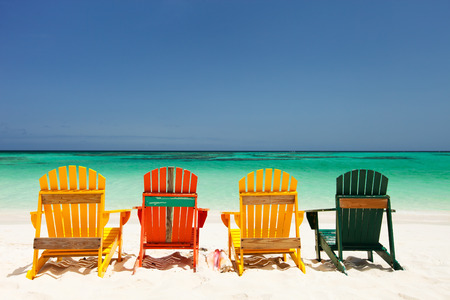 Row of colorful wooden chairs at tropical white sand beach in Caribbean