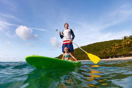 Father and his adorable little daughter paddling on stand up board having fun during summer beach vacation Stock Photo - 30070743