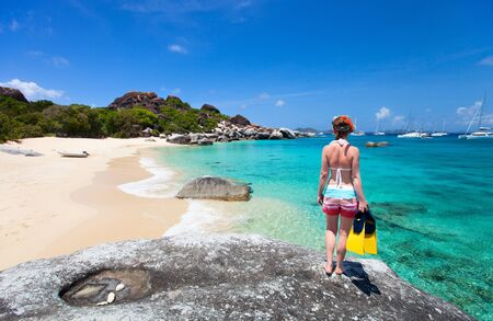 snorkelling: Young woman with snorkeling equipment enjoying view of a tropical beach standing on granite boulder at Virgin Gorda, British Virgin Islands, Caribbean