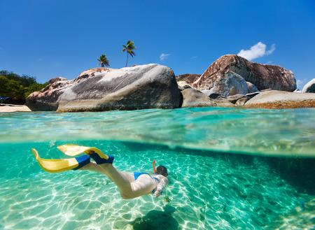Delat foto av ung kvinna som snorklar i turkos tropiskt vatten bland enorma granitblock p� badstranden, stor turistattraktion p� Virgin Gorda, Brittiska Jungfru�arna, Karibien Stockfoto