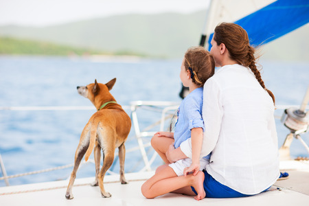 boating: Back view of mother, daughter and their pet dog sailing on a luxury yacht or catamaran boat