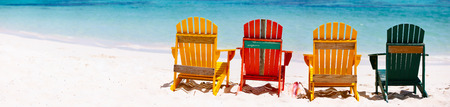 Row of colorful wooden chairs at tropical white sand beach in Caribbean, panorama with copy space perfect for banners photo