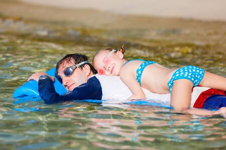 Father and his adorable little daughter on beach vacation relaxing on floating mat Stock Photo - 30071259