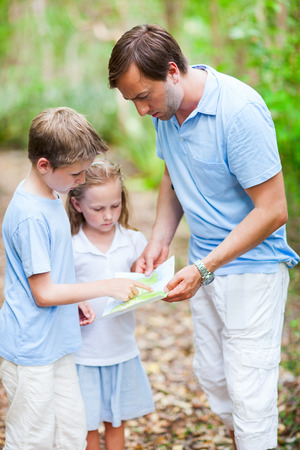 Family of father and little kids looking on map while hiking at forest or park Stock Photo - 30071291