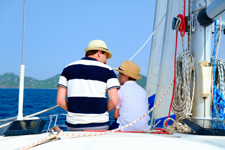 catamaran: Back view of father and son sailing on a luxury yacht or catamaran boat