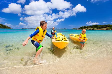 Gezin met kinderen peddelen op kleurrijke gele kajaks op tropische oceaan water tijdens de zomervakantie