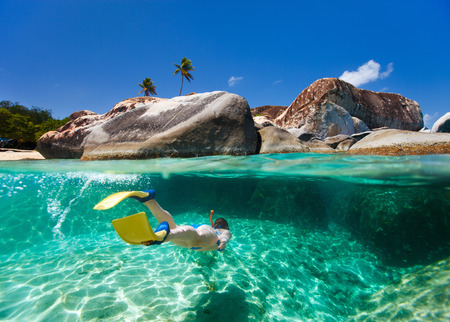 Delat foto av ung kvinna som snorklar i turkos tropiskt vatten bland enorma granitblock på badstranden, stor turistattraktion på Virgin Gorda, Brittiska Jungfruöarna, Karibien