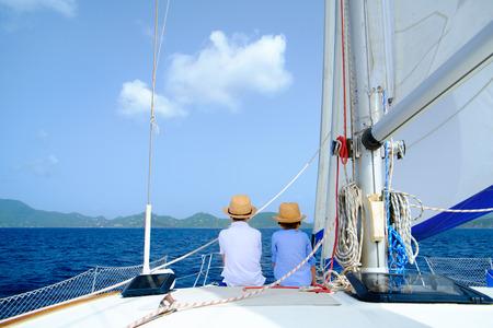 Back view of kids enjoying sailing on a luxury catamaran or yacht