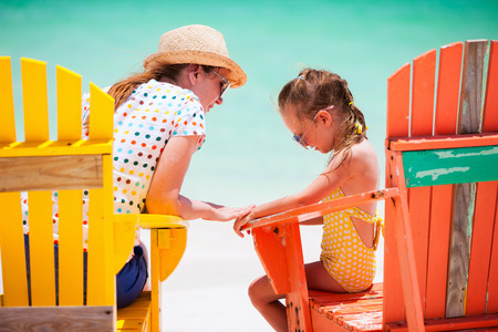 Mother talking to upset little daughter while sitting on colorful wooden chairs at tropical beach during summer vacation Stock Photo - 30305684