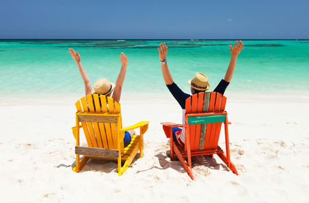 Happy couple sitting on colorful chairs at tropical beach enjoying Caribbean vacation Stock Photo - 30305694