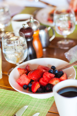 Delicious breakfast with fresh tropical fruits, berries and cup of hot coffee photo