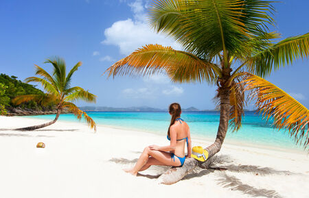 virgin girl: Back view of a young beautiful woman sitting on palm tree relaxing at white sand tropical beach