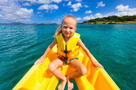 paddling: Little girl enjoying paddling in colorful yellow kayak at tropical ocean water during summer vacation