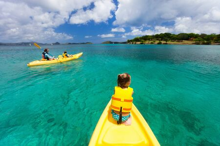 Family with kids paddling on colorful yellow kayaks at tropical ocean water during summer vacation Stock Photo - 30305705
