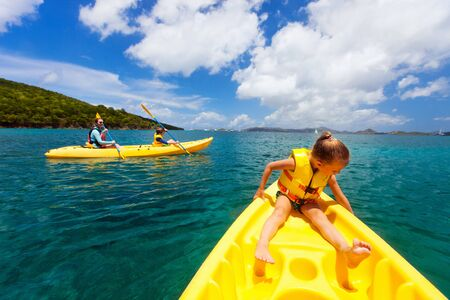 Family with kids paddling on colorful yellow kayaks at tropical ocean water during summer vacation Stock Photo - 30305711