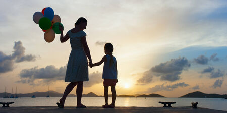 Silhouette of happy mother and her little daughter with bunch of balloons on sea coast at sunset Stock Photo - 30305714