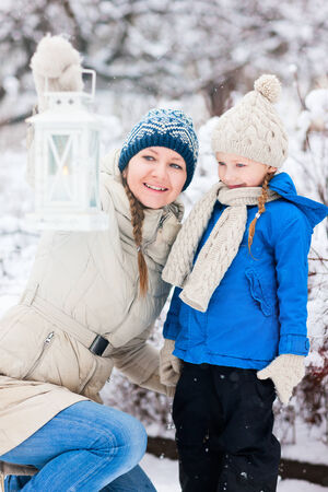 Family of mother and her adorable little daughter with Christmas lantern outdoors on beautiful winter snow day photo