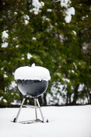 cold season: Black barbeque grill covered with snow outdoors on winter day Stock Photo