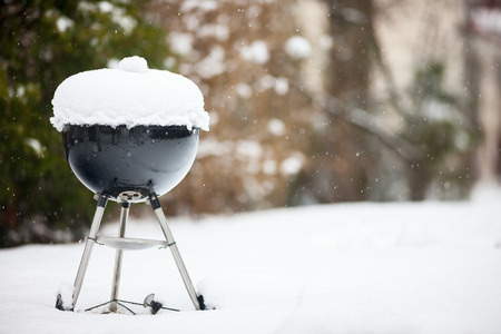 Black barbeque grill covered with snow outdoors on winter day Stockfoto