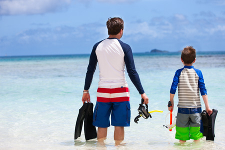 Back view of father and son with snorkeling equipment fins and mask at tropical beach photo