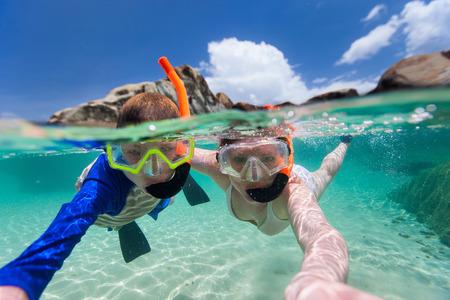 Split foto av mor och son familj snorkling i turkosa havet vatten vid tropisk ö