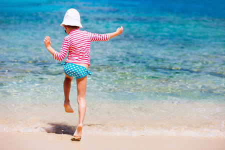 Little girl in a colorful sun protection swimwear on vacation splashing in a shallow water at tropical beach