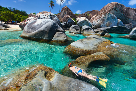 the virgin islands: Young woman snorkeling in turquoise tropical water among huge granite boulders at The Baths beach area major tourist attraction on Virgin Gorda, British Virgin Islands, Caribbean Stock Photo