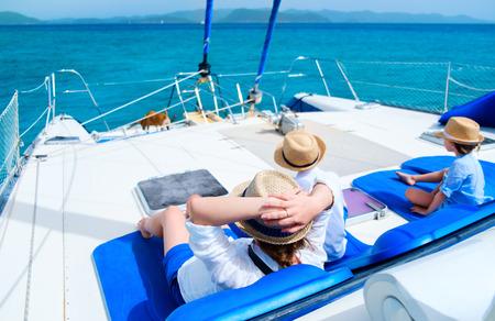 Vista posteriore della madre ei suoi bambini che si distendono con grande vela momento in yacht di lusso o in barca catamarano