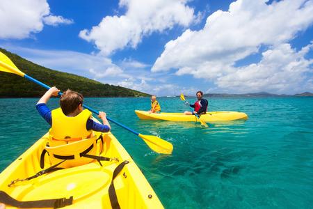 ocean kayak: Familia con ni�os remar en kayaks amarillos coloridos en el agua del oc�ano tropical durante las vacaciones de verano