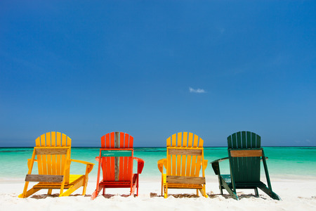 Row of colorful adirondack wooden chairs at tropical white sand beach in Caribbean
