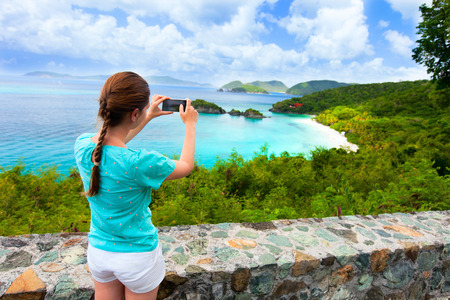 virgin girl: Back view of tourist girl taking photo with mobile cell phone of Trunk bay on St John island, US Virgin Islands considered by many as most beautiful beach in Caribbean