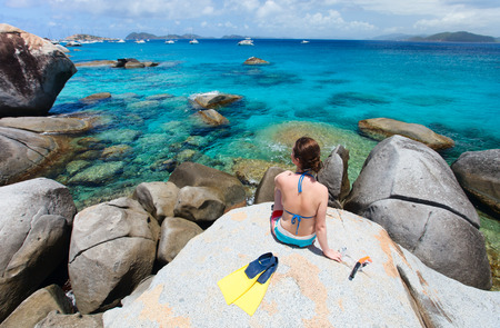 Young woman with snorkeling equipment enjoying aerial view of a tropical beach sitting on granite boulder at Virgin Gorda, British Virgin Islands, Caribbean Stock Photo - 30607912