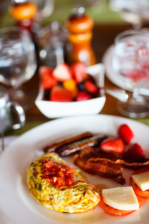 Delicious breakfast with omelet, fresh tropical fruits, berries and cup of hot coffee photo