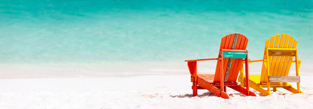 Two colorful wooden chairs at tropical white sand beach in Caribbean, panorama with copy space perfect for banners Stock Photo