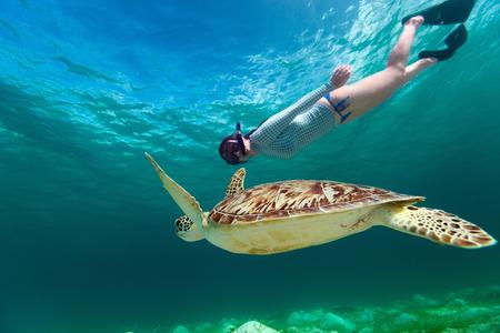 Onderwater foto van een jonge vrouw snorkelen en zwemmen met Hawksbill zeeschildpad