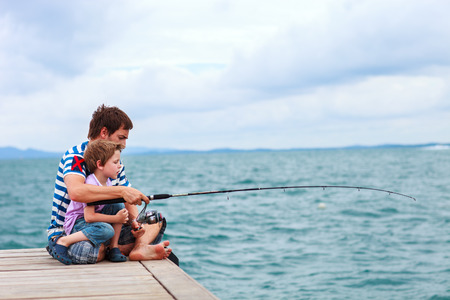 Father and his little son fishing together from wooden jetty photo