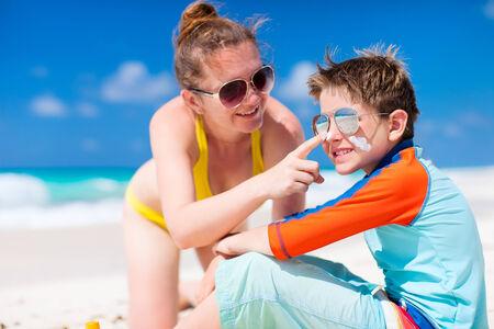 Mutter Anwendung Sonnenschutzcreme, um ihren Sohn am tropischen Strand während der Sommerferien