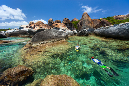 virgin: Family of young mother and son snorkeling in turquoise tropical water among huge granite boulders at The Baths beach area major tourist attraction on Virgin Gorda, British Virgin Islands, Caribbean