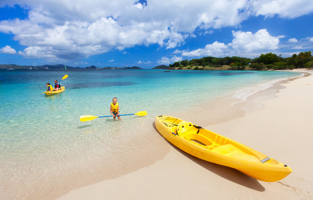 Family with kids paddling on colorful yellow kayaks at tropical ocean water during summer vacation photo