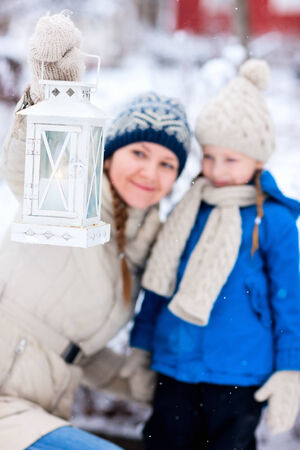 Family of mother and her adorable little daughter with Christmas lantern outdoors on beautiful winter snow day, selective focus on lantern photo