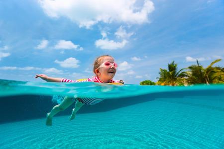 Spalato fotografia subacquea di adorabile bambina con giallo anello gonfiabile di nuoto in una piscina in vacanza estiva
